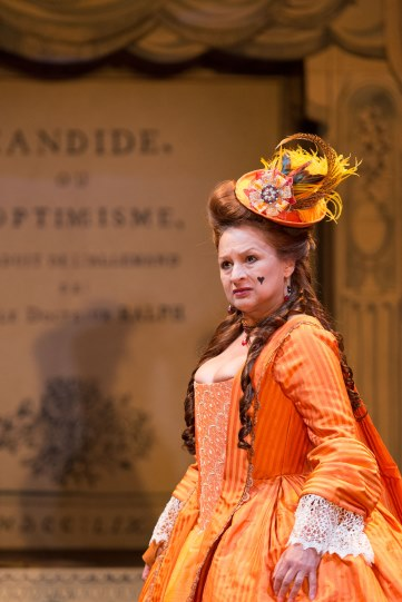 Ishia Bennison as Countess in Candide wearing period orange dress