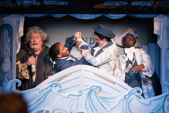 Ian Redford as Pangloss, Kevin Harvey as Jacques, Ciarán Owens as Sailor and Dwane Walcott as Candide (The Actor) in Candide in a cardboard boat