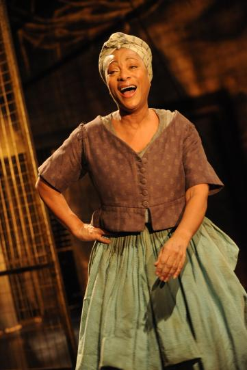 Dona Croll as Juanita, wearing a green skirt and brown cardigan