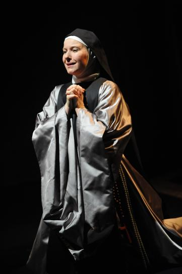 Teresa Banham as Sister Sebastiana, wearing silver robes and a black wimple