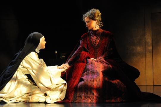 A nun kneels at the feet of a woman in a red dress