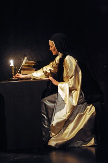 Catherine McCormack as Sister Juana, writing at her desk in the light of a candle