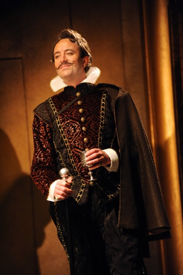 Simon Thorp as Don Hernando, in a black outfit with white ruff and a rakish moustache