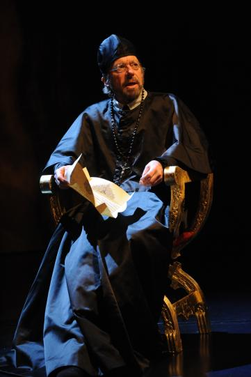Stephen Boxer as Archbishop Aguiar Y Seijas, wearing priest's robes and rosary beads