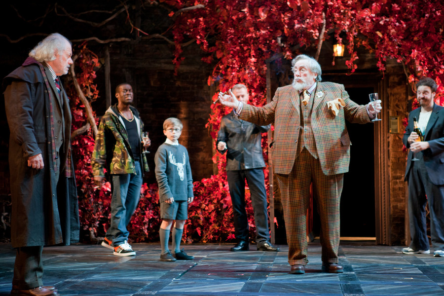 Sir John Falstaff stands among the crowd in a red garden, a wine glass in hand