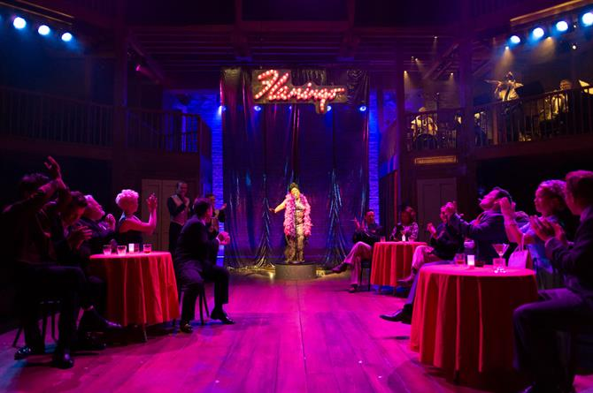 An image of A Mad World My Master showing a vibrant purple room with three tables, an audience and a performer at the back-centre of the image