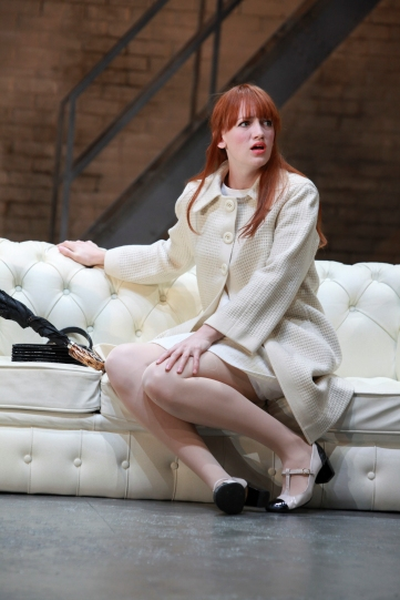 Lucy Briggs-Owen as Helena, seated on a white sofa in a matching white coat.