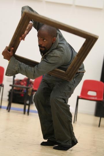 A man climbs through a wooden picture frame.