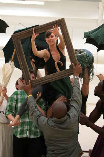 A group of people hold up a woman, who leans through a wooden frame.