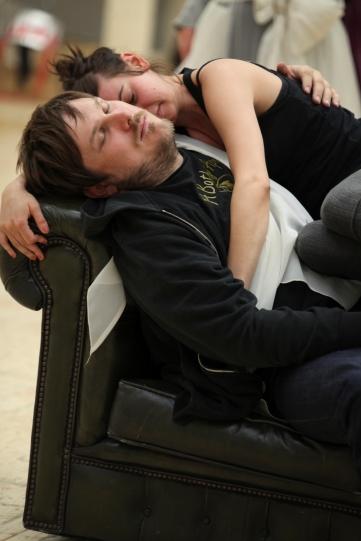 A man and woman sleep on a black leather sofa.