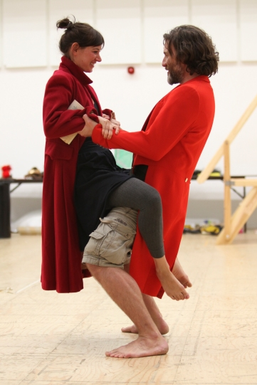 A man lifts up a woman. Both are dressed in bright red coats.
