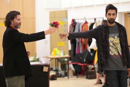 A man hands a pink flower to another man.