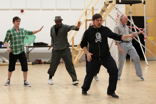 A group of actors practise a dance in rehearsals.