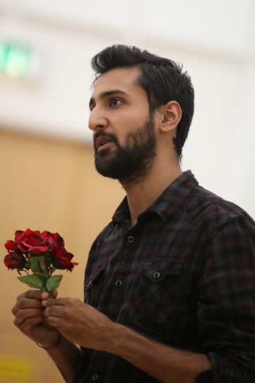 A man holds a small red flower in front of his chest.