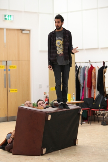 A man stands on an upturned sofa as other actors hide behind it.