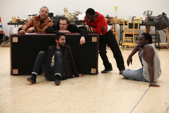 A group of men chat around an upturned sofa.