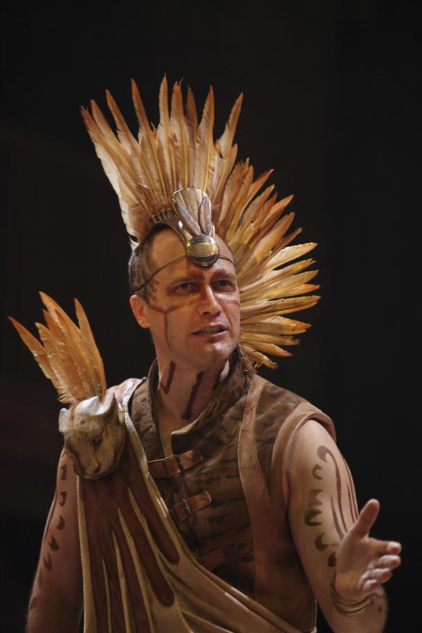 Man wearing a brown Aztec-style costume with a feathered headdress