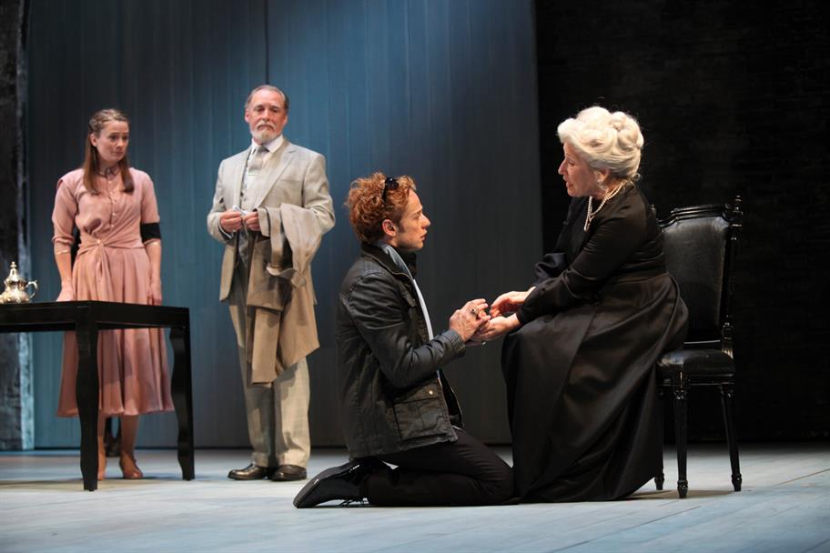 The Countess, wearing a black dress, holds her son's hand. Bertram is kneeling on the floor and looking up at her.