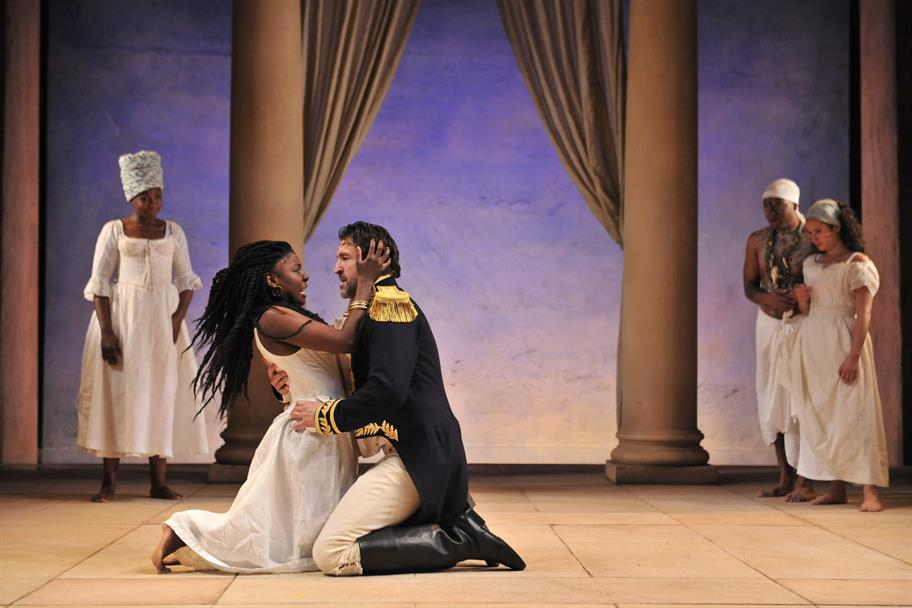 Antony in uniform embraces Cleopatra on the floor