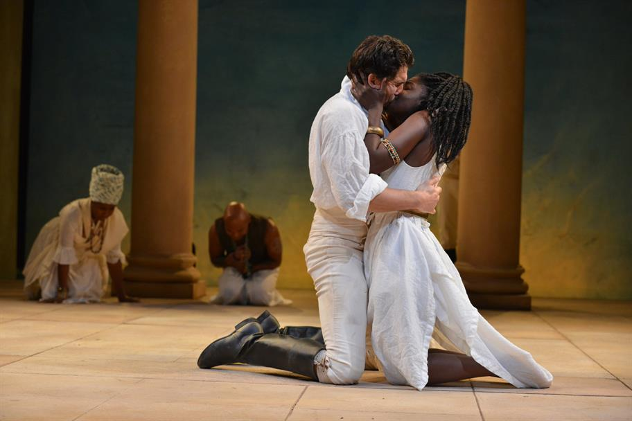 Cleopatra (Joaquina Kalukango), wearing a white slip, kisses Mark Antony (Jonathan Cake), who is wearing a white outfit and black boots