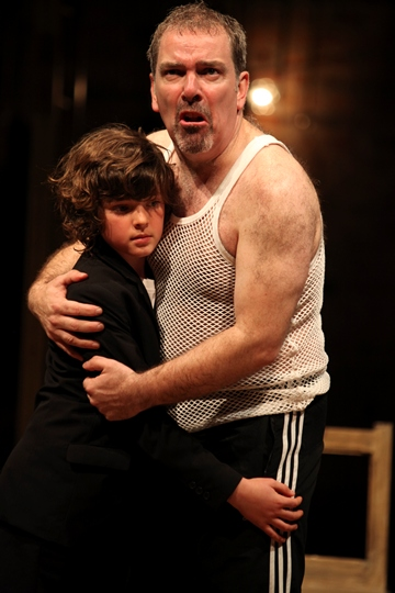 Man wearing jogging bottoms and a string vest, clutching a young boy and looking horrified