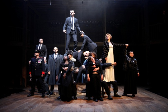 A group of men and women in dark clothes pose on stage.