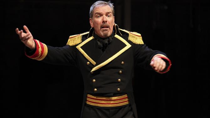 Lloyd Hutchinson as Boris Godunov, wearing a black military coat with red and gold decorations