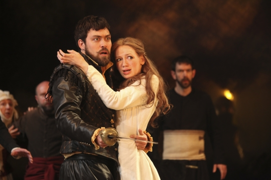 A woman in white holds onto a man in black, who holds a rapier
