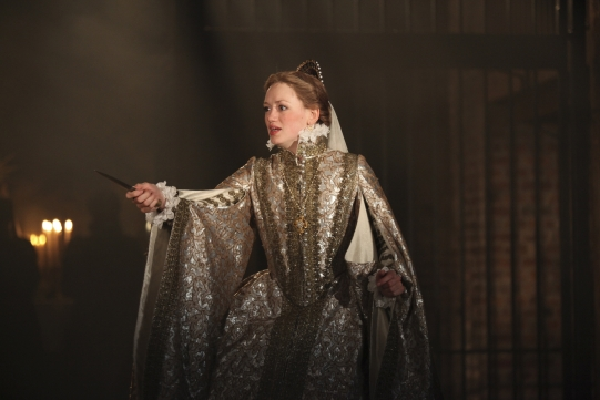 Lucy Briggs-Owen in Cardenio holding out a dagger, wearing an opulent gown.