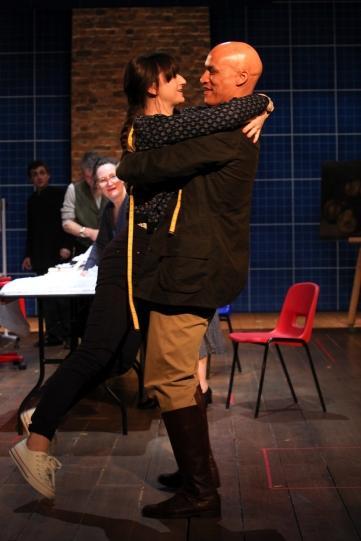 A man lifts a woman off her feet in an embrace