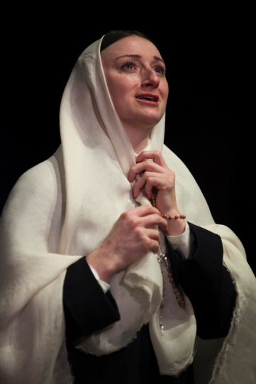 Jodie McNee as Virginia in a white head scarf, holding rosary beads