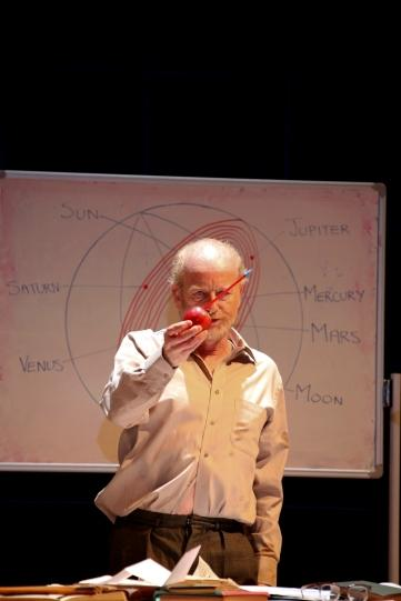 Ian McDiarmid as Galileo standing in front of a whiteboard holding an apple