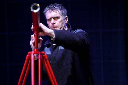 Paul Hamilton as Federzoni in A Life of Galileo pointing a telescope