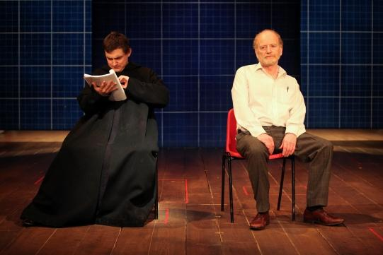 Joel Gillman as Little Monk sits next to Ian McDiarmid as Galileo