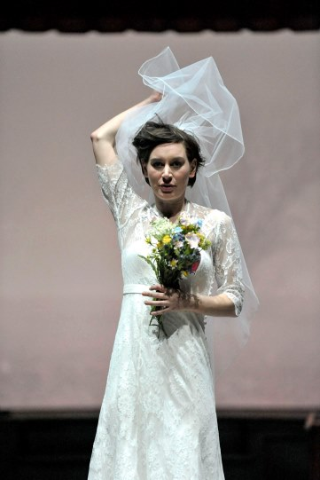 Pippa Nixon as Ophelia in Hamlet wearing a wedding dress lifting her veil up with one hand