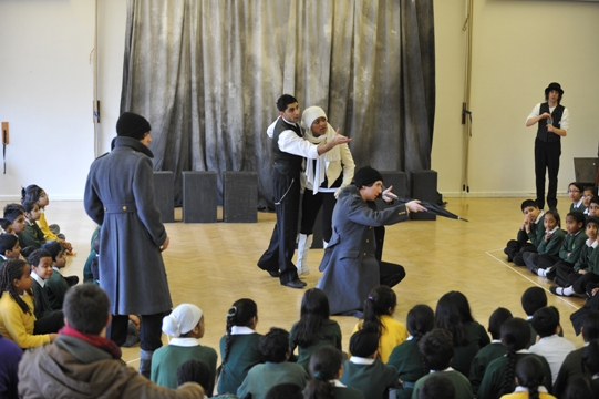 The company of Hamlet acts on stage watched on by school children