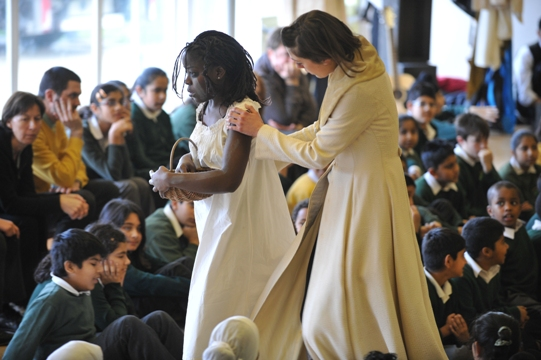Two women stand amongst a crowd in school hall as children and teacher watch on