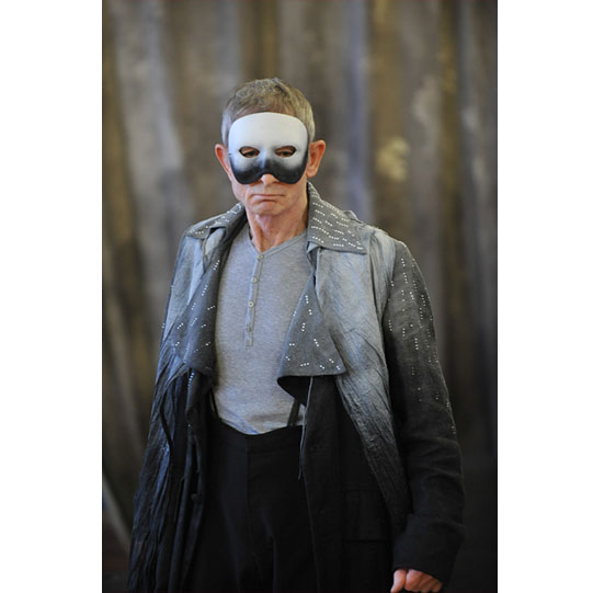 Man dressed in grey and black, wearing a mask that covers most of his face
