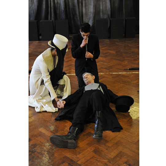 A man and woman grieve over another man who lies still on the floor