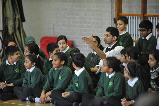 Actor sits amongst children in a school hall pointing to something in the distance