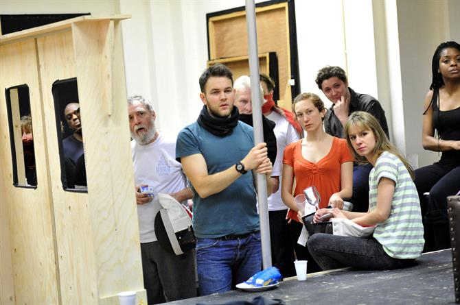 The cast of Hamlet in rehearsal, standing around mock ups of the scenery