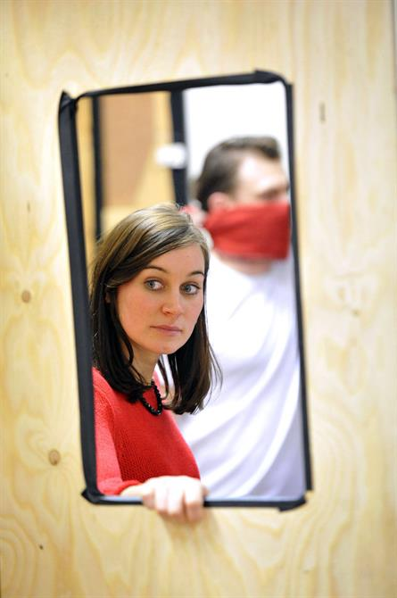 Pippa Nixon in rehearsal for Hamlet, looking through a hole in a temporary wooden wall