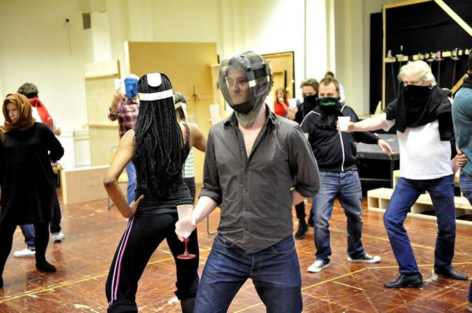 The cast of Hamlet in rehearsal, posing as if dancing, most with their faces covered