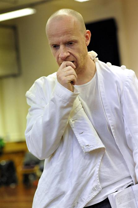 Jonathan Slinger, all in white, holds a hand to his mouth as if distressed