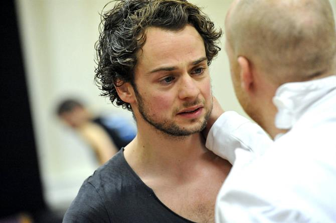 A man in white with his back to camera has a hand on the shoulder of a man with dark curly hair