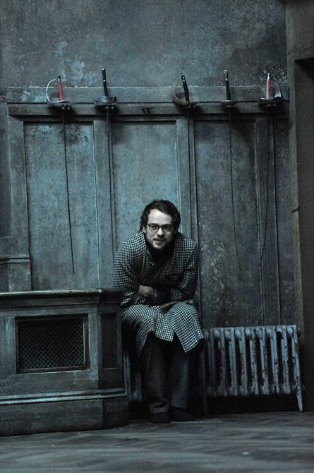 Alex Waldmann as Horatio, huddled up next to a radiator with swords hanging on the wall above him