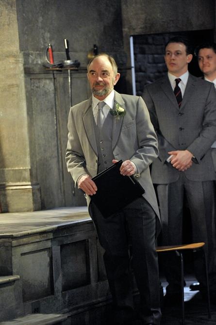 Robin Soans as Polonius, holding a clipboard and wearing a grey wedding suit