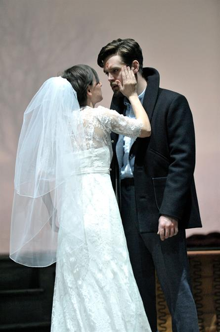 Pippa Nixon as Ophelia and Luke Norris as Laertes. Ophelia is dressed as a bride, and strokes her brother's face