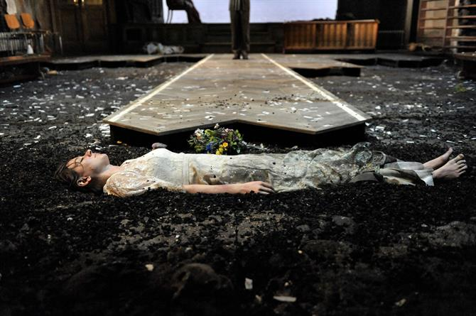 Pippa Nixon as Ophelia in Hamlet in a dirty wedding dress lying dead in the mud