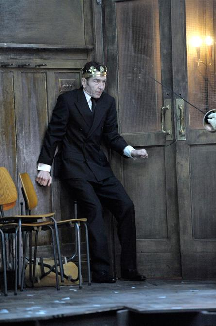 Greg Hicks as Claudius, wearing a crown and looking afraid as a sword is pointed at him